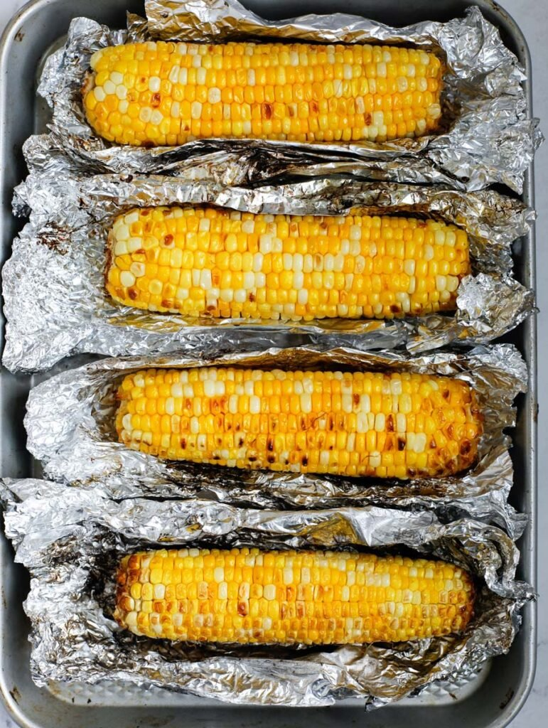 Grilled corn wrapped with tinfoil on a sheet pan.