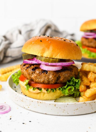 A homemade burger on a plate with toppings and fries.