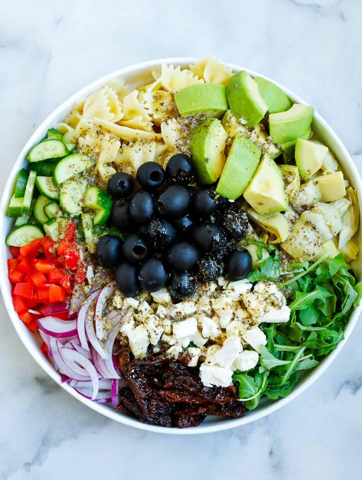 Salad dressing added to a bowl of Mediterranean salad.