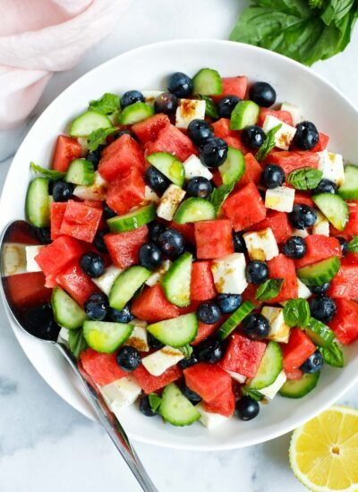 top down shot of watermelon feta salad in a bowl with a spoon