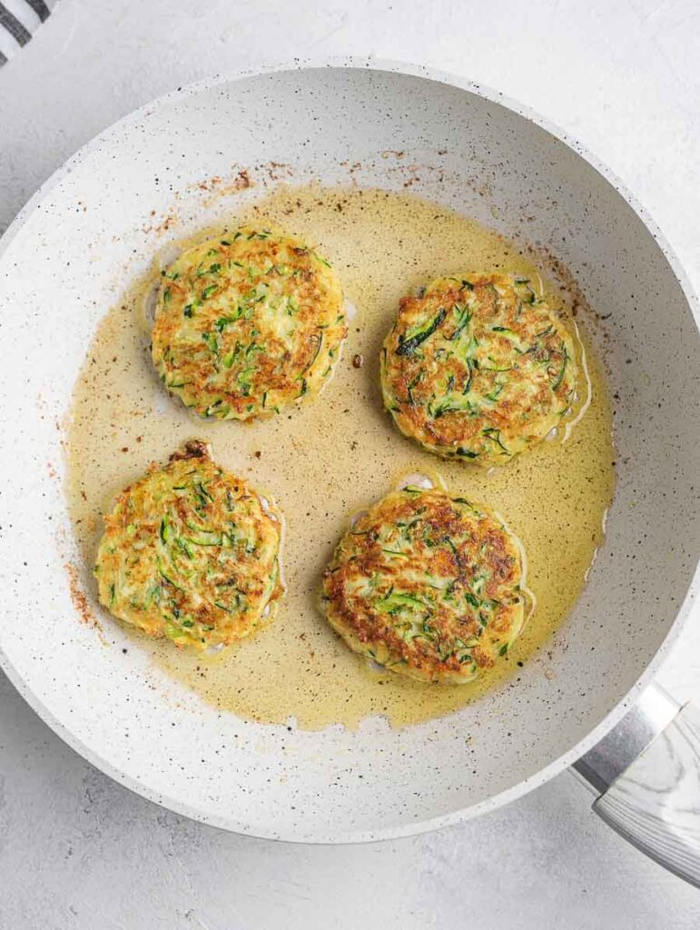 zucchini fritters being fried in a pan