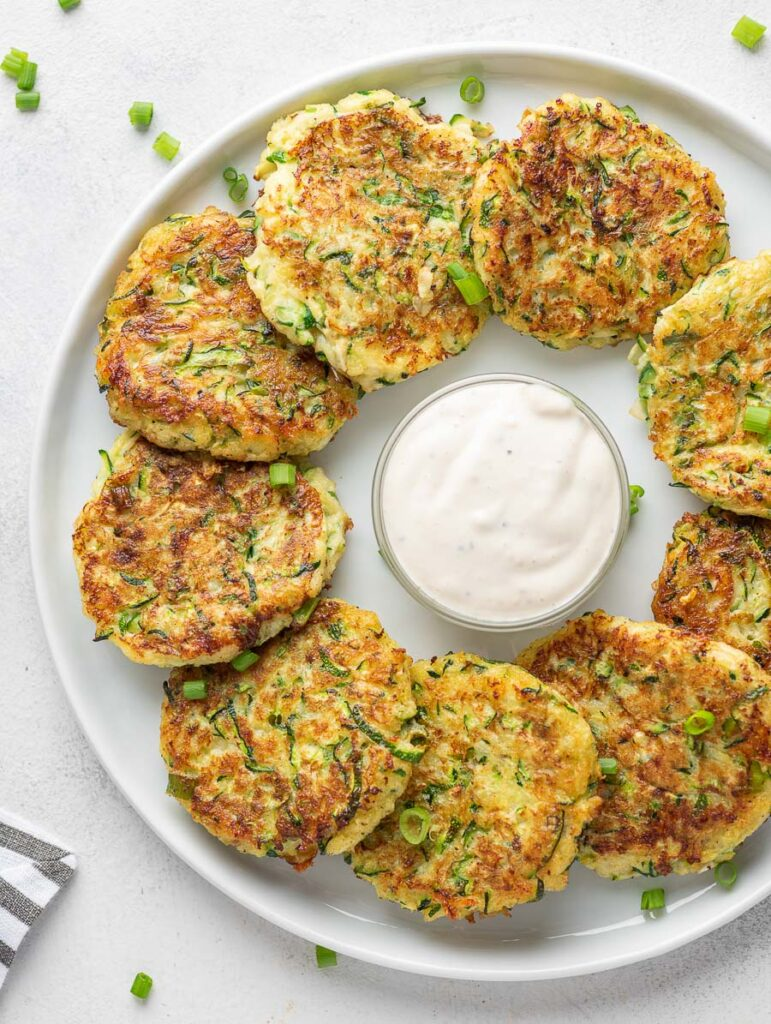 zucchini fritters on a white plate with dipping sauce