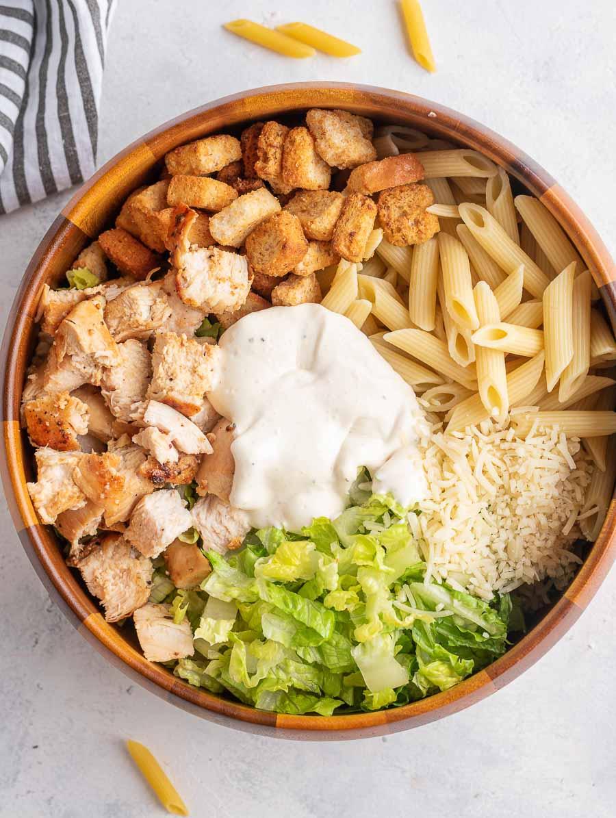 ingredients of chicken ceasar pasta salad in a wooden bowl