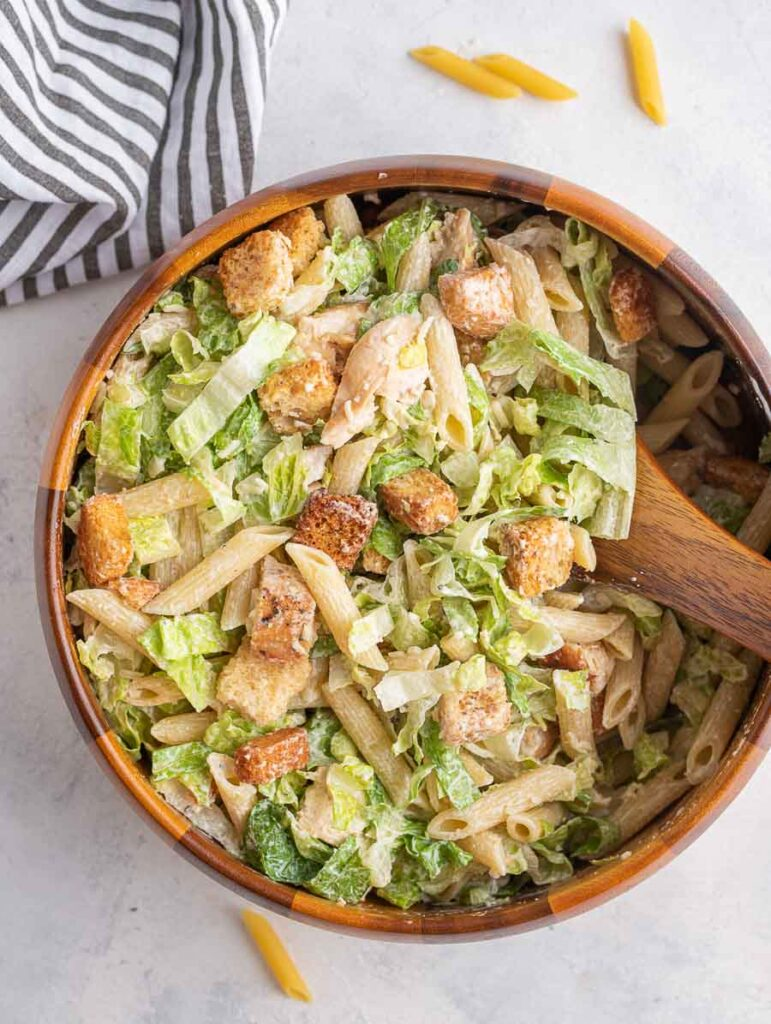 chicken ceasar pasta salad in a wooden bowl