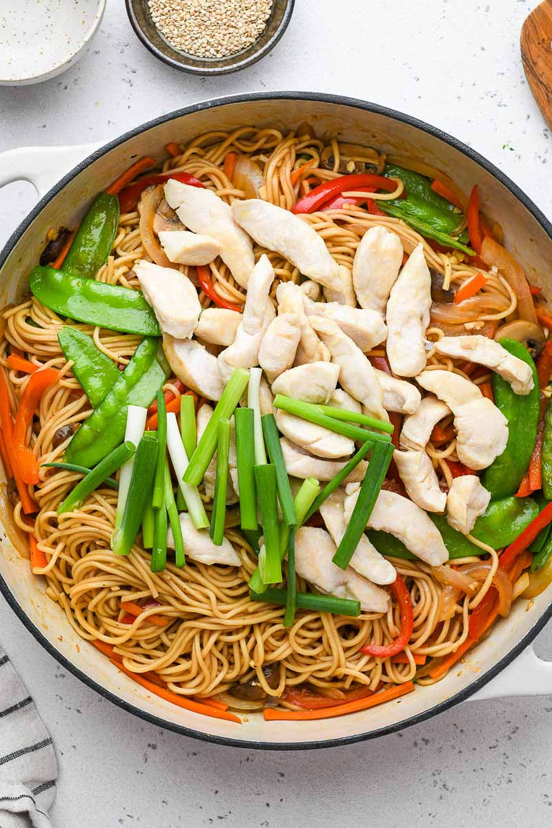 chicken and veggies in a skillet on top of the lo mein noodles