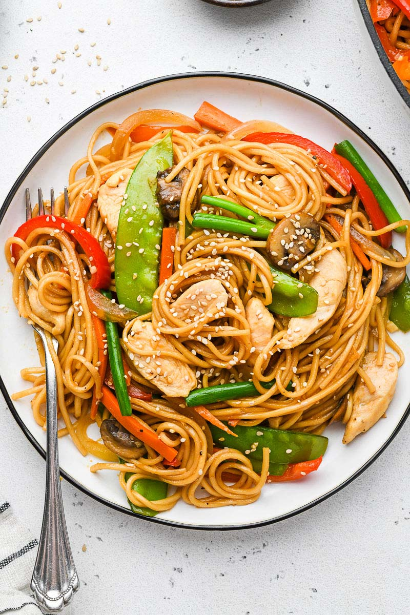 chicken lo mein on a plate i with a fork