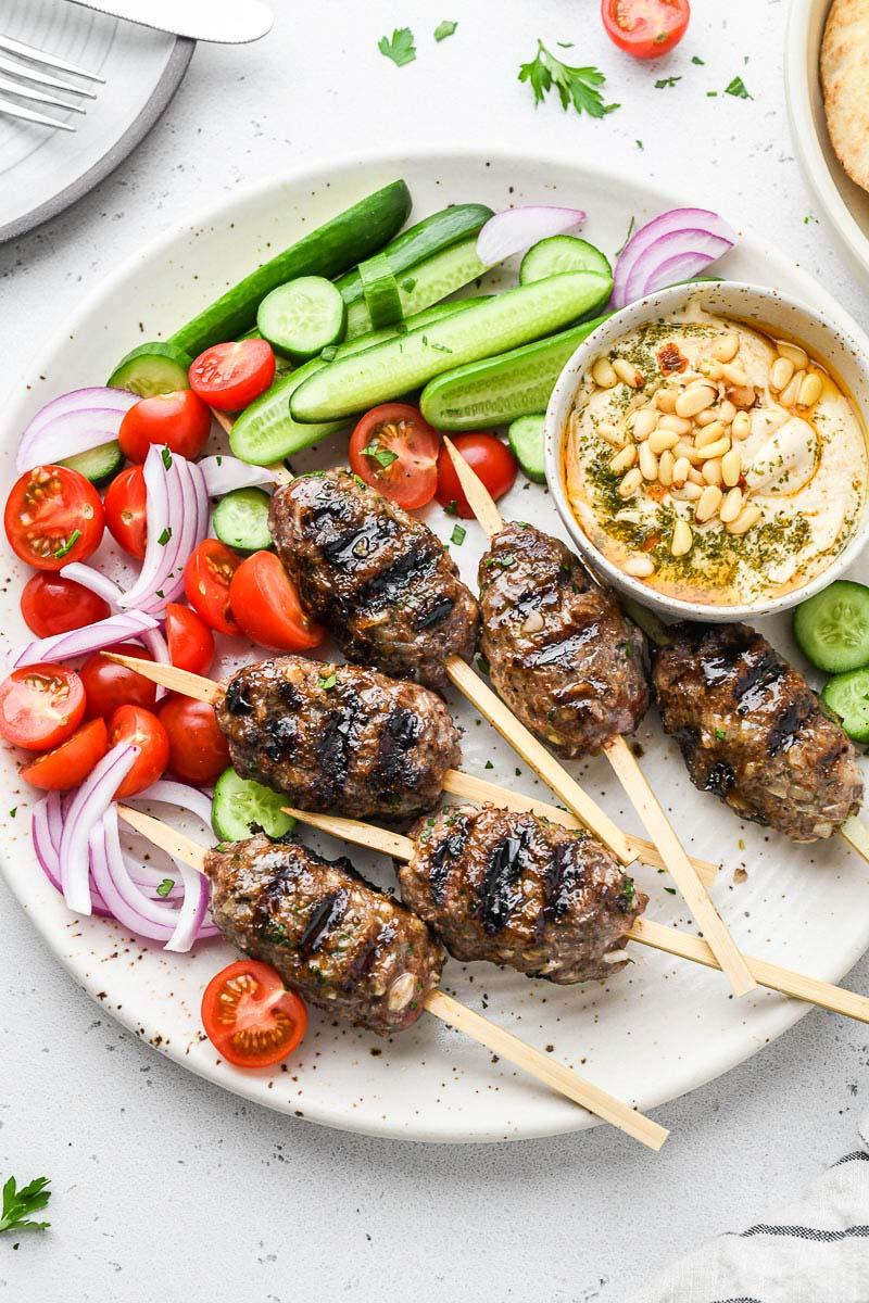 beef kofta skewers on a plate with veggies and hummus