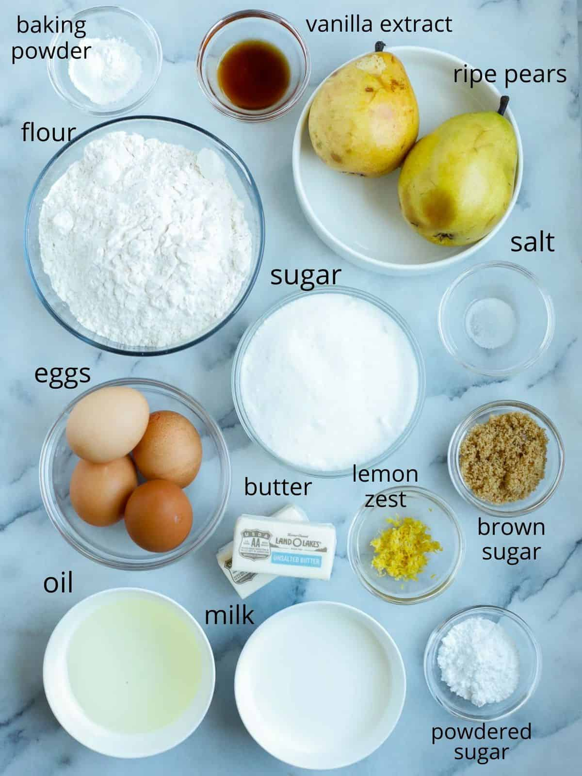 ingredients of the pear cakes in ramekins laid out on a marble slab.