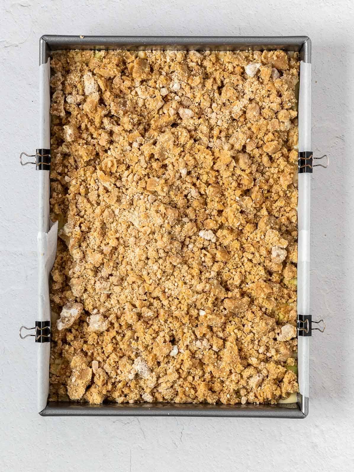 apple crumb cake before baking in a rectangular pan