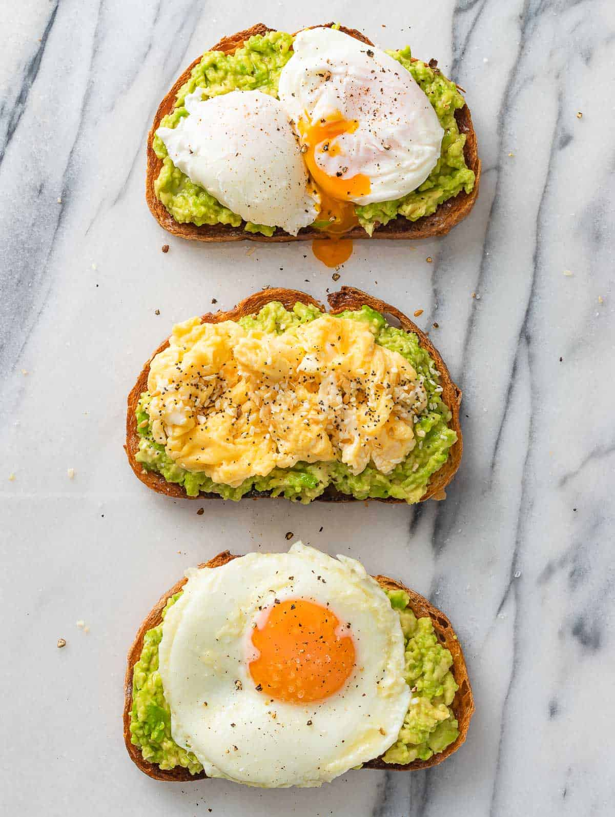 3 avocado toasts topped with fried, scrambled and pouched egg.