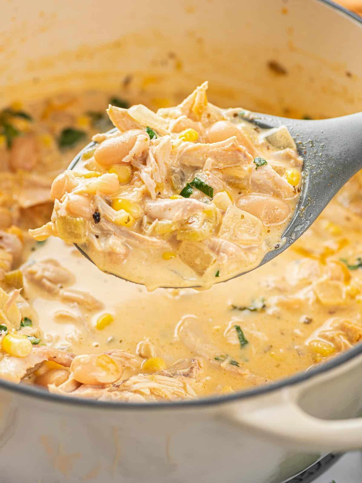 a spoon of white chicken chili scooped out of the pot