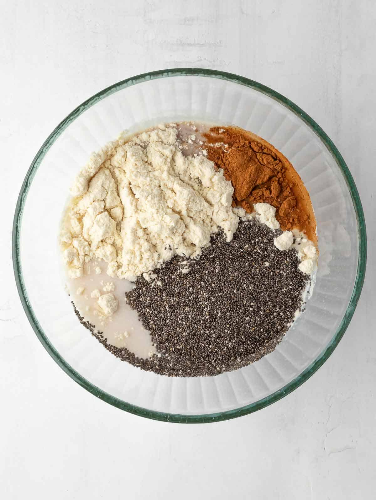 all ingredients of the cinnamon apple Overnight Chia pudding in a bowl before mixing