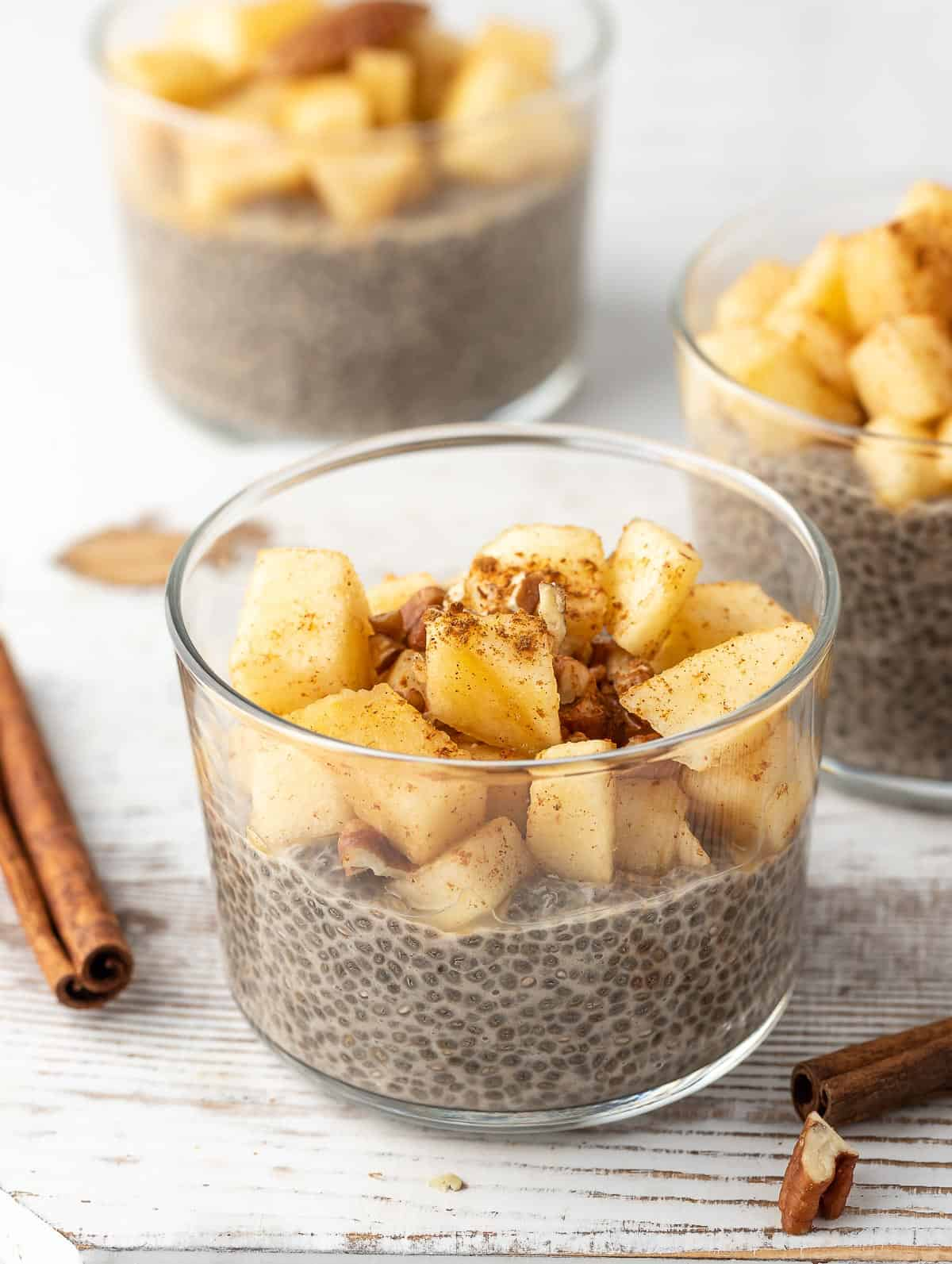 Overnight Chia Pudding topped with apples and cinnamon sticks on the side of the bowl.