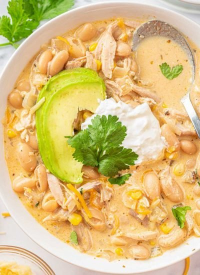 white chicken chili recipe on a white plate, topped with sour cream and avocado