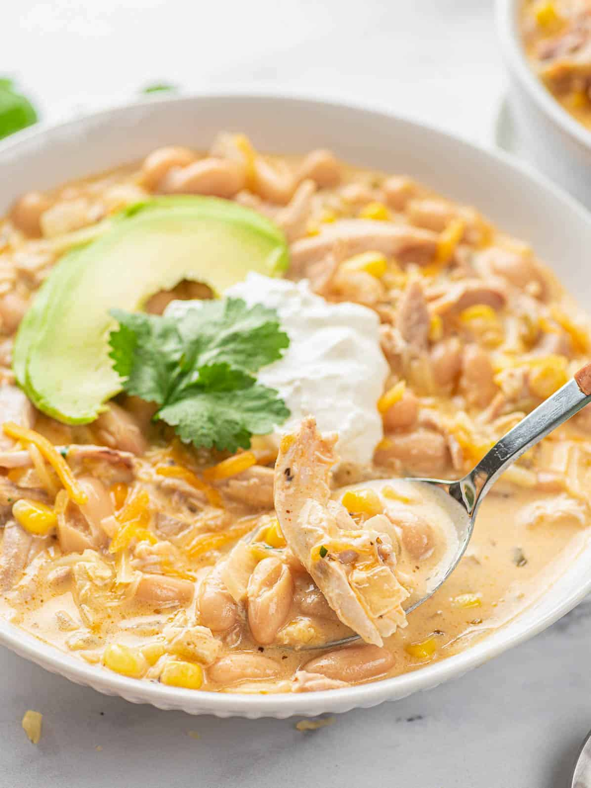 spoon scooping white chicken chili from plate