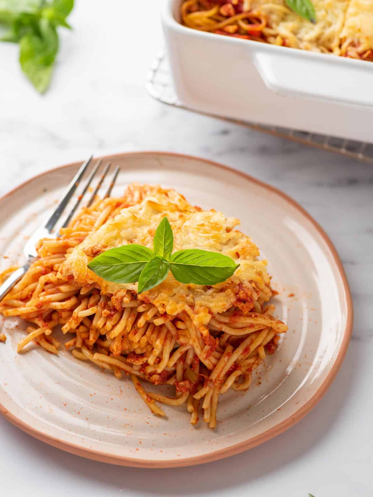 portion of baked spaghetti pasta served on a plate and topped with basil leaves.
