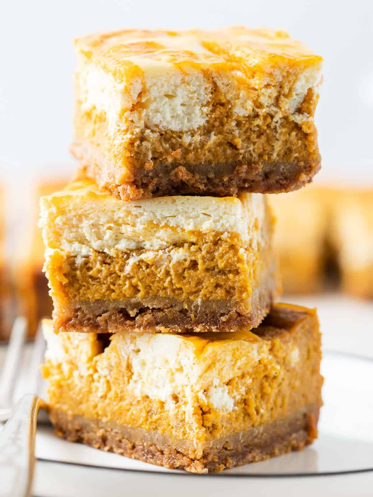 3 stacks of the pumpkin cheesecake bars in a close up shot