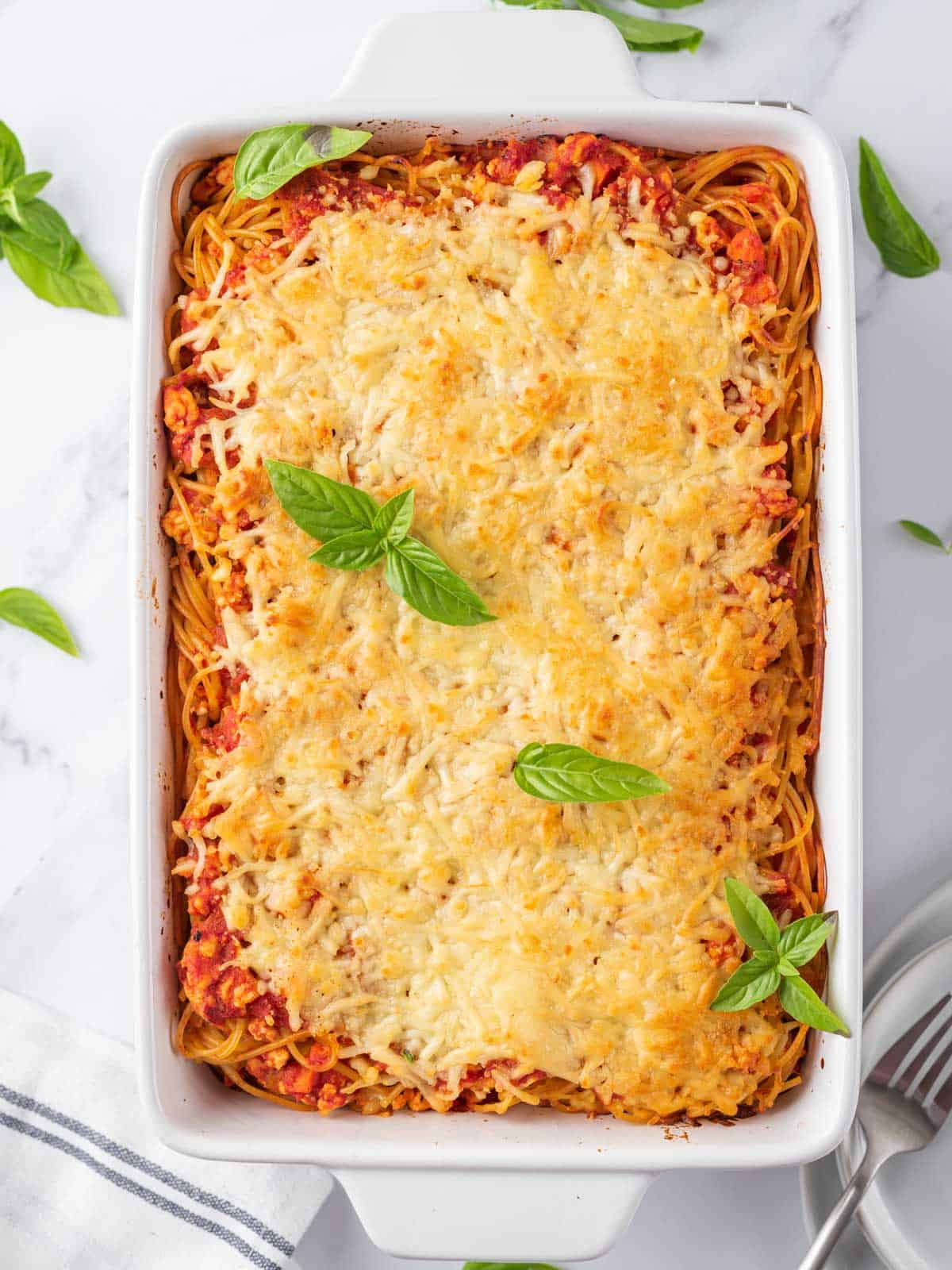 Easy Spaghetti Pasta Bake after cooking, topped with basil leaves.